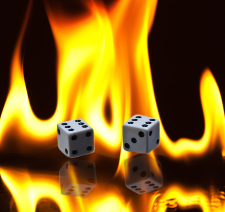 A pair of dice with double sixes lying amidst burning flames with reflection