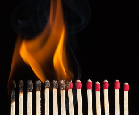 A line of red safety matches showing burnt out matches on the left , through burning matches, ignition, and unused ones on the right.