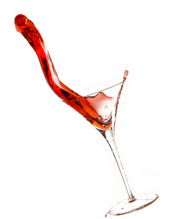 Wine being poured into glass, with slop spilling over. Stock Photo