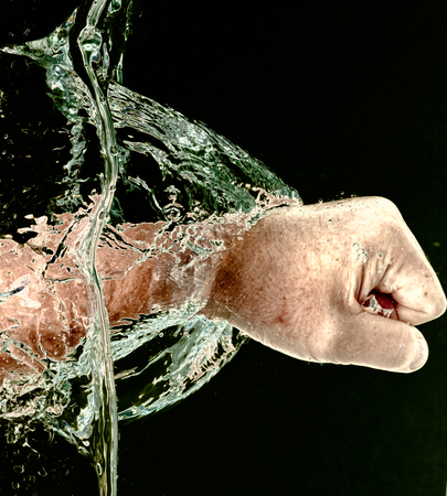 displacement: Punching Through Water - Close-up of a mans fist punching through water horizontally, display of movement and force against black.
