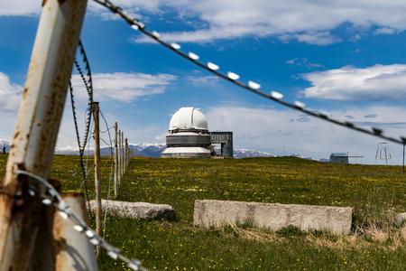 Assy-Turgen observatory across field, behind razor wire fence