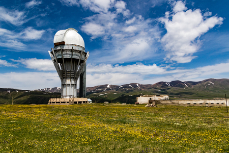 Assy-Turgen observatory full tower with mountain range and clouds behind Reklamní fotografie