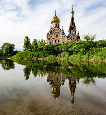 Christian church near Almaty, Kazakhstan reflected in lake