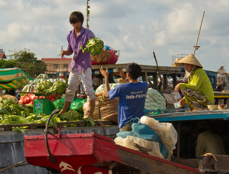 South Vietnam - Oct 17, 2011: Man buy cabbage from a boat at the Can Tho floating market Editorial