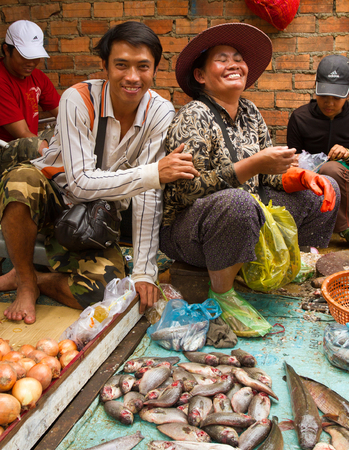 fish vendor: Siem Reap, Cambodia - Oct 15, 2011: Friendly vendors share a laugh at a market
