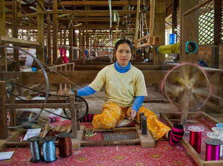 Siem Reap, Cambodia - Oct 11, 2011: Woman creating thread at a silk factory Редакционное