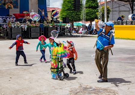 San Bartolome, Ecuador Aug 24, 2017 - Children chase giant bubbles created by bubble wand vendor