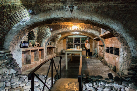 Tbilisi, Georgia - June 6, 2017: Woman stands in historic wine cellar, where Stalin hid while being chased by the army. Editorial