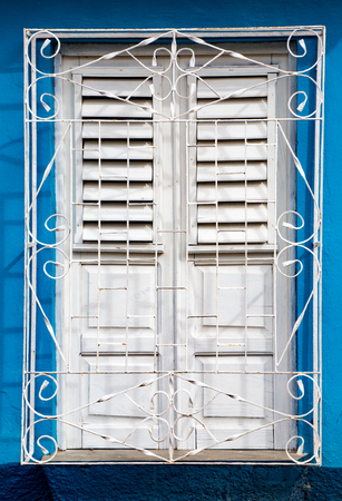 Newly painted white shutters on window behind white metal grill on bright blue wall in Trinidad, Cuba Stock Photo