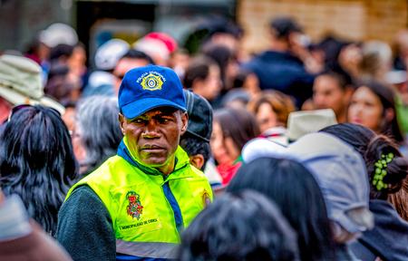 Cuenca, Ecuador - Dec 24, 2014: A security officer scans the crowd at a festival Editorial