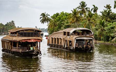 ALLEPPEY, INDIA, MAR 13, 2018: Bamboo thatched houseboat floats down the backwaters of Kerala