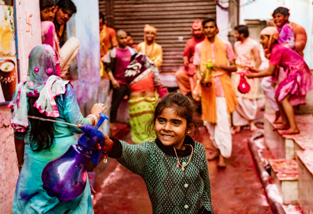 Nandgeon, India, Holi Festival, Feb 25, 2018 - Girl sprays people with paint filled water while smiling, along with others in background