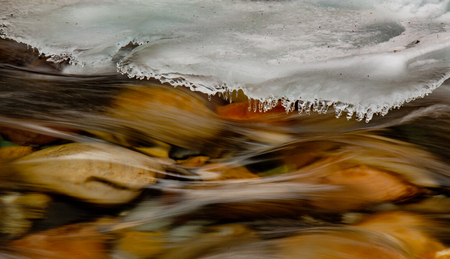 Background texture of river running swiftly under growing shelf of ice Banque d'images