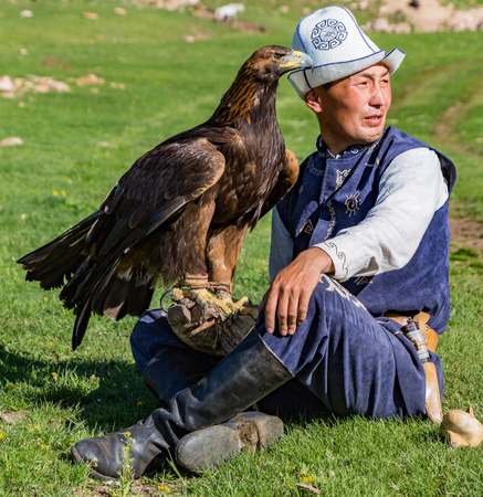 Issyk Kul, Kyrgyzstan - May 29, 2017: Eagle Hunter holds his eagles, sitting on the ground