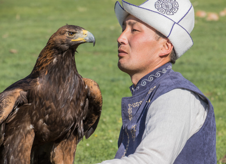 Issyk Kul, Kyrgyzstan - May 29, 2017: Eagle Hunter holds his eagles on horseback Editorial