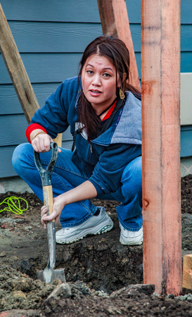 Oakland, California, USA - Dec 3, 2010: Woman digs post hole for Habitat For Humanity, Kinsell Commons