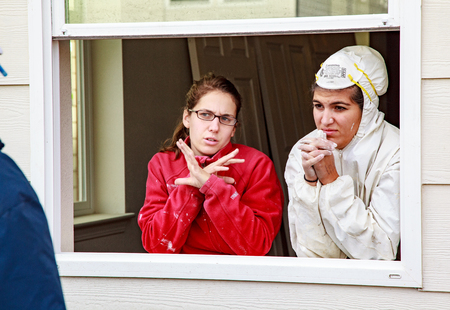 Oakland, California, USA - Dec 3, 2010: Two women discuss construction details while standing in window frame for Habitat For Humanity, Kinsell Commons Editoriali