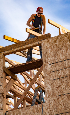 Oakland, California, USA - Jan 22, 2011: Man builds roof for home for Habitat For Humanity. El Rincon
