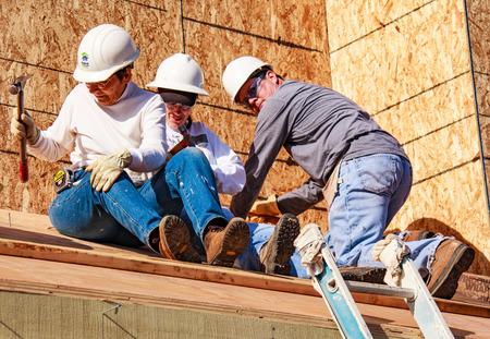 Oakland, Californie, USA - 22 janvier 2011: Trois personnes construisent un toit pour la maison d'Habitat pour l'humanité. El Rincon