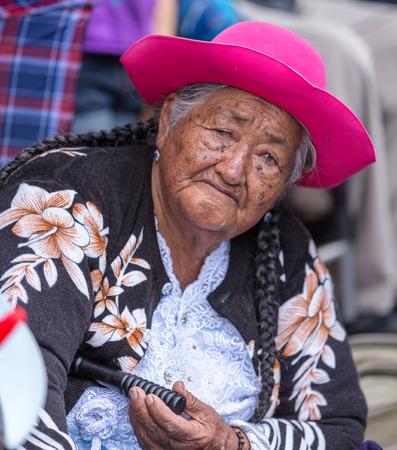 Elderly woman sits on sidewalk watching Christmas parade in Cuenca, Ecuador on Dec 24, 2013