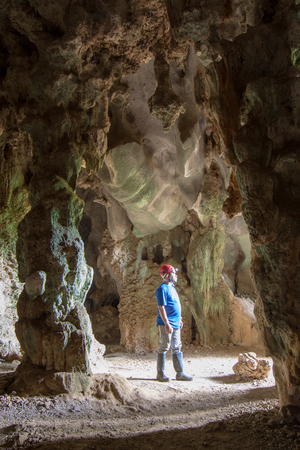 Vinales, Cuba, Nov 24, 2017 - Man stands in Santo Tomás Cave, visible from shaft of light from opening