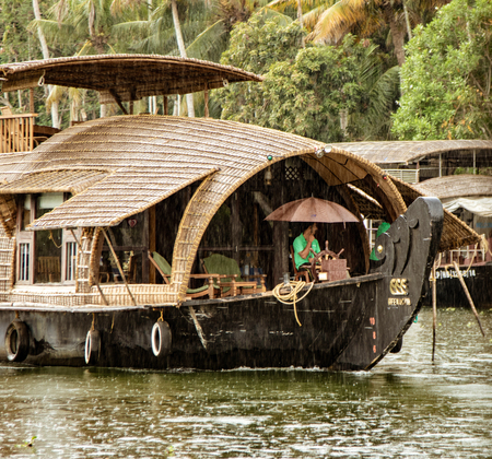 ALLEPPEY, INDIA, MAR 13, 2018: Bamboo thatched houseboat floats down the backwaters of Kerala in the rain