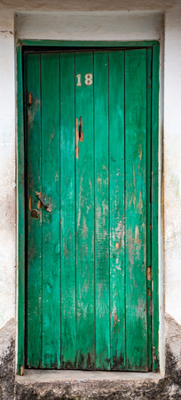 Trinidaad, Cuba Nov 26, 2017 - chipped and broken green door on white wall