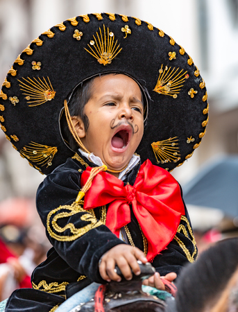 Cuenca, Ecuador - Dec 24, 2014: A young boy yawns on horseback in the Paseo del Nino parade