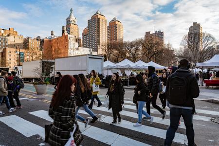 New York City, New York, Feb 14, 2018: People cross street with New York City skyline in the background