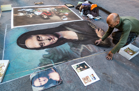 Florence, Italy - Apr 23, 2017: Man paints the Mona Lisa in chalk on the street Editorial