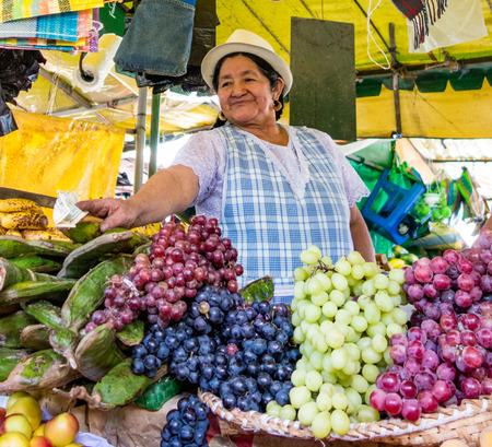 Cuenca, Ecuador - 30 de diciembre de 2012: Mujer vendiendo frutas en la tienda (mercado) Editorial