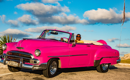 Havana, Cuba, Nov 20, 2017 - Driver sits in a pink Classic American Chevrolet, with sky and clouds in the background