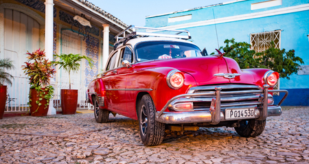 Trinidad, Cuba, Nov 28, 2017 - Red Classic 1950's Chevrolet is parked in front of a home 報道画像