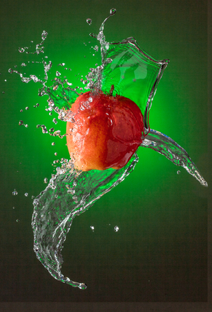Water Splashes on Red Apple Stock Photo - 104580671