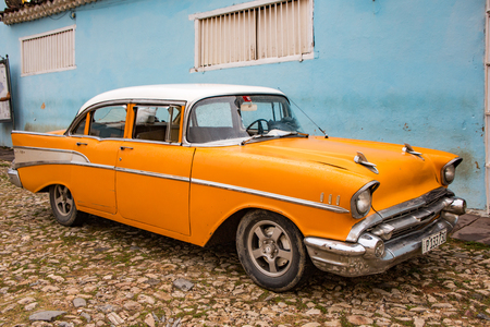 Trinidad, Cuba, Nov 28, 2017 - Orange Classic 1950s Chevrolet is parked in front of a home