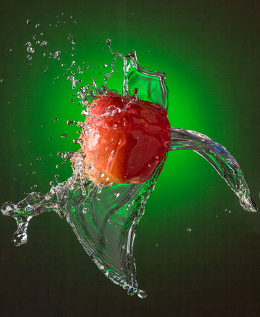 Water Splashes on Red Apple Stock Photo - 104581059