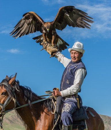 Issyk Kul, Kyrgyzstan - May 29, 2017: Eagle Hunter holds his eagles on horseback, ready to take flight