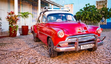 Trinidad, Cuba, Nov 28, 2017 - Red Classic 1950s Chevrolet is parked in front of a home