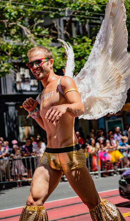 SAN FRANCISCO, CALIFORNIA, JUNE 24, 2018:  GAY PRIDE PARADE - Corporate Smirnoff liquor marches with angles on stilts
