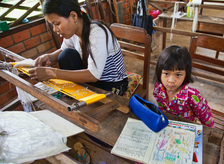 Angkor, Cambodia  Oct 11, 2911: Woman creating thread at a silk factory with her daughter studying nearby 에디토리얼