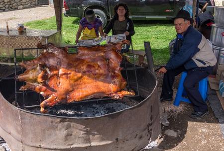 Cuenca, Ecuador / Nov 22, 2012: Man BBQs full pig splayed out for easier cooking Editorial