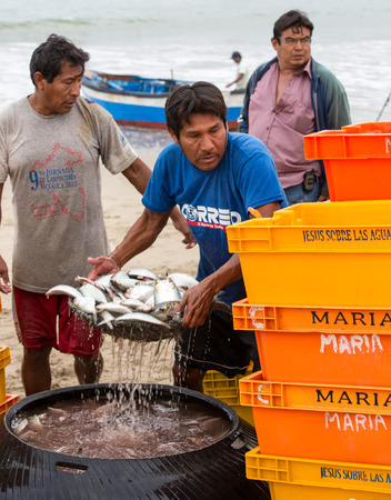 Puerto Pizarro, Ecuador  Aug 20, 2014: man transfers bin of fish to scale to be paid Redakční