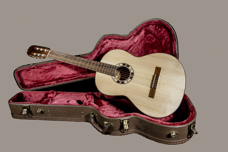 Acoutic guitar sits in a red velvet lined case Stok Fotoğraf