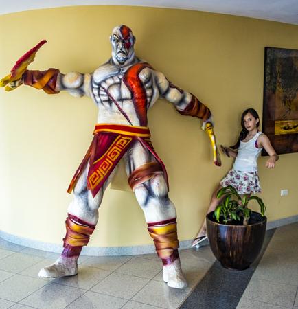 Salinas, Ecuador  December 31, 2015 - girl retrieves her ball behind a huge paper mache warrior destined to be burned at midnight