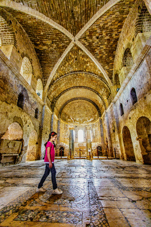 Demre, Turkey / September 4, 2016 - Girls walks across the vestibule of the church of St Nicholos, believed to be the source of the Santa Claus myth Editorial