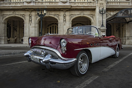 Havana, Cuba - November 21, 2011 - Classic red Buick parked in front of a Havana museum