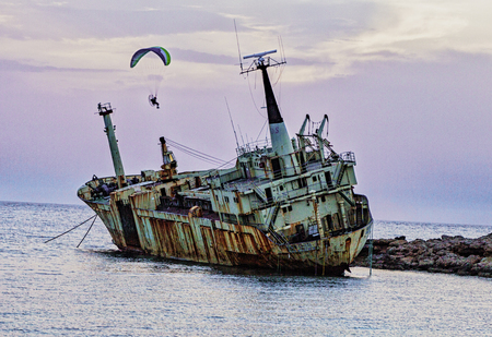 Pathos, Cyprus / May 21, 2016 - Person uses powered paraglide to circle a shipwreck near the shore
