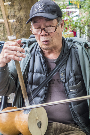 New York, New York  Nov 4, 2014: Man plays traditional Chinese musical instrument Editorial