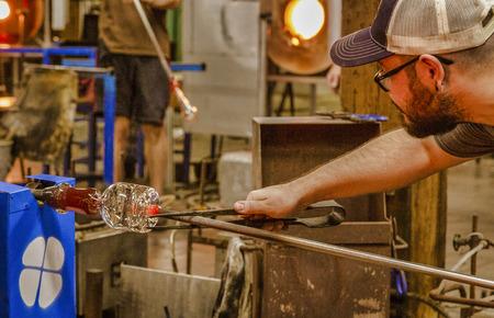 Woodstock, Vermont - October 13, 2018 - Craftsman creates glass bottle in workshop