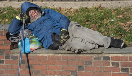 Boston, Massachusetts - October 25, 2018 - Homeless man sleeps on a brick wall in a park Editorial